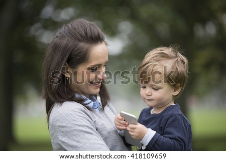 Young boy playing with his mothers smart phone.
