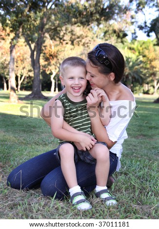Young boy playing with mother at park