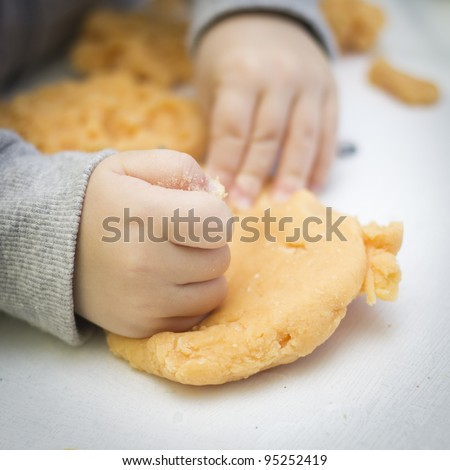 Young boy playing with playdough - stock photo