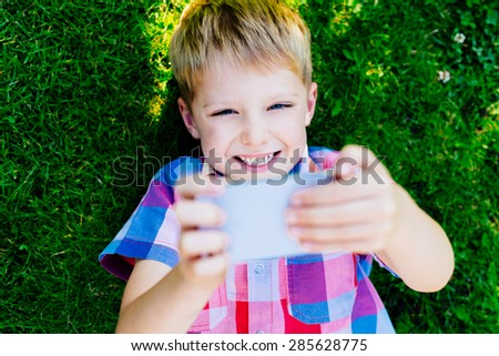 Young boy playing with smartphone, laying on grass - stock photo