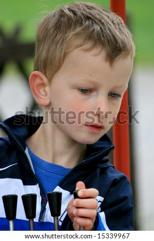 Young boy playing with the controls of a toy in a park