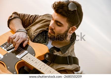 young boy plays guitar at sunset - stock photo