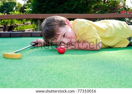 Young boy plays mini golf on putt putt course. - stock photo