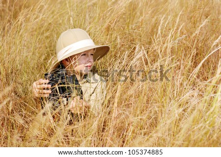 Young boy plays safari explorer with binoculars and bush hat in a field. happy adventure seeking kid playing outdoors. - stock photo
