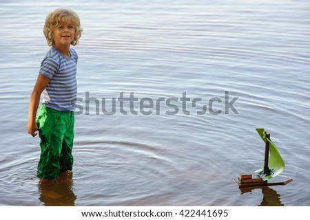 Young boy plays with homemade sailing boat. He stands in calm lake water. He looks at the camera. - stock photo