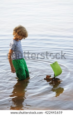 Young boy plays with homemade sailing boat. He stands knee deep in water and moves his knees back and forth to create waves that move the boat. - stock photo