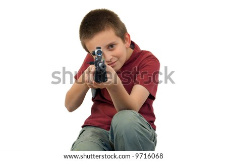 young boy pointing gun at camera, focus on boys face, isolated - stock photo