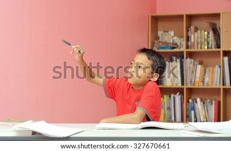 young boy pointing hand to the right during studying  - stock photo