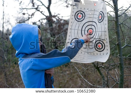 Young boy pointing out bullseye shot while holding rifle - stock photo