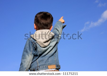 Young boy pointing with his finger to the blue sky - stock photo