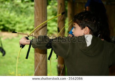 Young boy poised with bow and arrow about to shoot across the field, outdoors. - stock photo