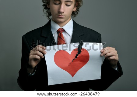 Young boy portrait holding a broken paper printed with a heart - stock photo