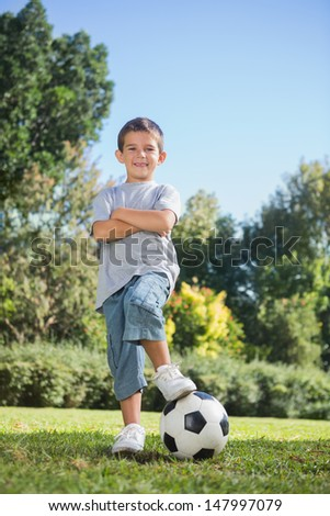 Young boy posing with football in the park smiling at camera