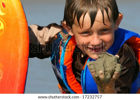 Young boy posing with his boogie board and holding sand in his hand - stock photo