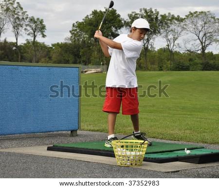 young boy practicing golf swing at the driving range - stock photo