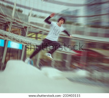 young boy practicing parkour in a urban area. radial blur effect. concept about extreme sports - stock photo