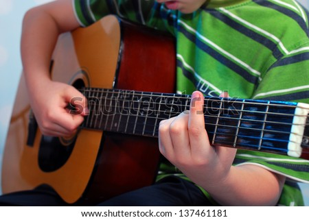 young boy practicing playing the classical guitar - stock photo