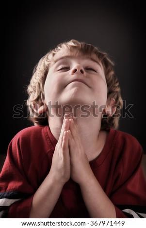 Young boy praying - stock photo