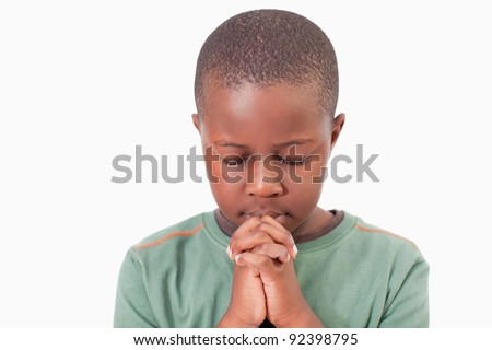 Young boy praying against a white background - stock photo