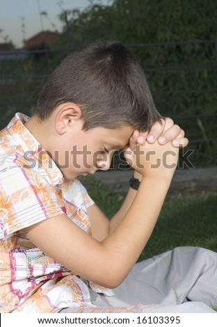 Young boy praying outdoors - stock photo