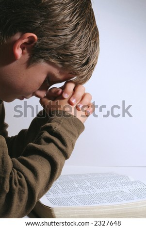 Young boy praying over the bible - stock photo