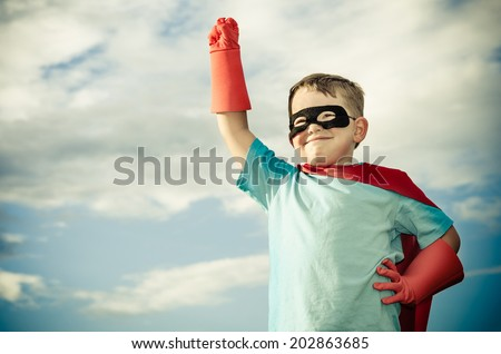 Young boy pretending  to be superhero in vintage filtered image - stock photo