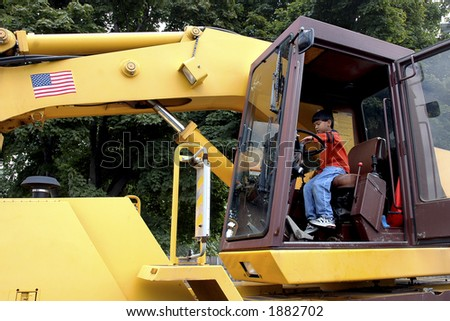 Young boy pretending to drive a giant earth mover - stock photo