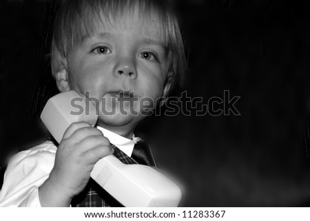 Young boy pretending to use the phone, businessman - stock photo