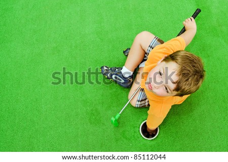 Young boy pulling ball out of hole while playing miniature golf - stock photo