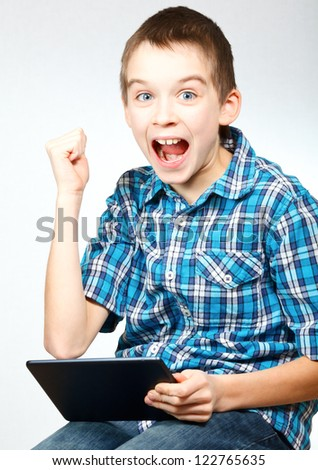 Young boy pumps his fist and cheers holding a touch pad - stock photo