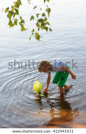 Young boy pushes his homemade sailing boat in the calm lake water. It is summertime. - stock photo
