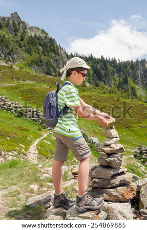 Young boy put stone on small pyramid at mountain trail in summer Alps - stock photo