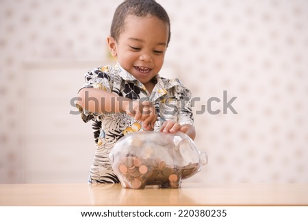 Young boy putting money in piggy bank - stock photo