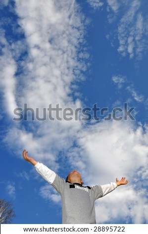 young boy raising hands up to the sky, space for copy