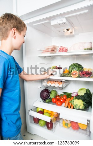 Young Boy Reaching for Snack in Refrigerator Full of Healthy Food Options - stock photo