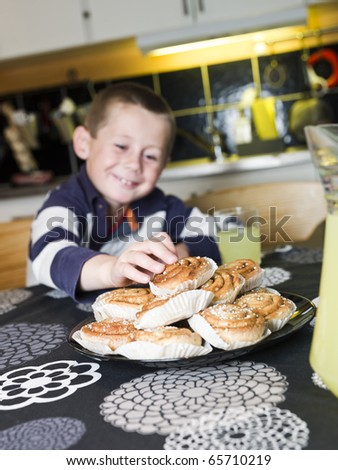 Young Boy reaching for sweets in the kitchen - stock photo