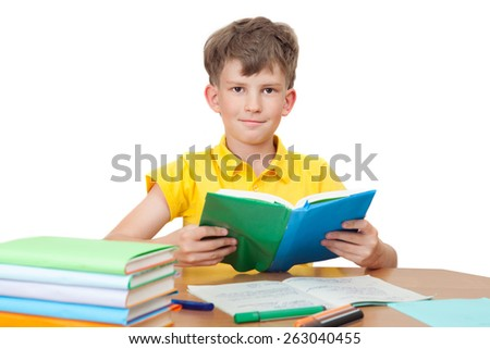 Young boy reading book at table, isolated on white background - stock photo