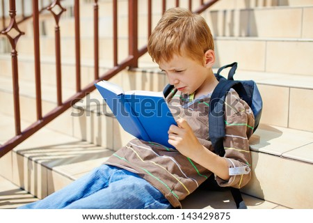 Young boy reading book on school stairs - stock photo