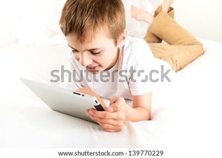 Young Boy Reading Book on Tablet Device - stock photo