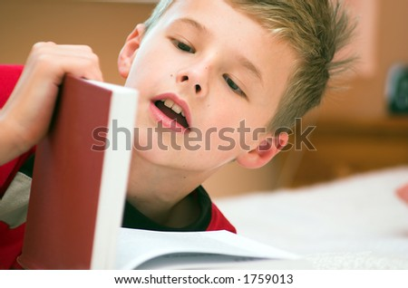 Young boy reading book on the bed - stock photo