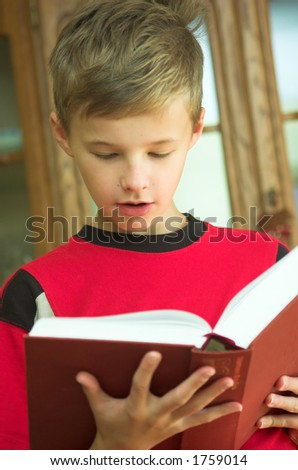 Young boy reading old, heavy book