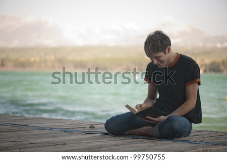 Young boy reading on a pier - stock photo
