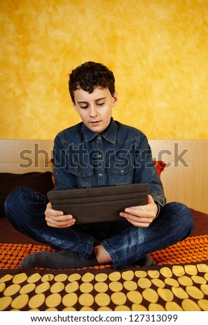 Young boy reading on digital tablet, cross-legged on bed - stock photo