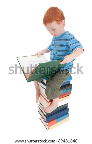 Young boy reading on top of tall pile of books. Isolated on white. - stock photo