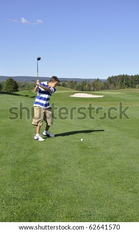 Young boy ready to drive a golf ball on a golf course. - stock photo
