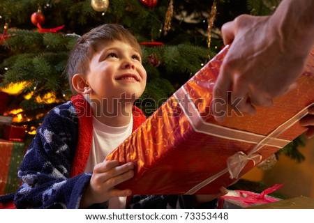Young Boy Receiving Christmas Present In Front Of Tree - stock photo