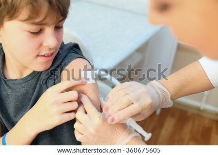 Young boy receiving vaccination immunisation by professional health worker, focus on shoulder