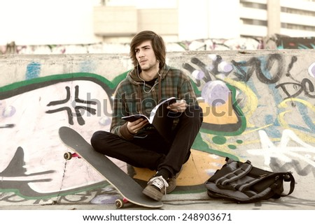 Young boy relaxing at the skate park - stock photo