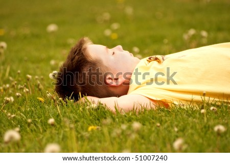 Young Boy Relaxing On Grassy Field - stock photo