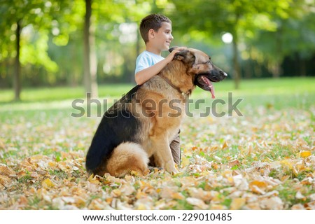 young boy relaxing with  German Shepherd in park